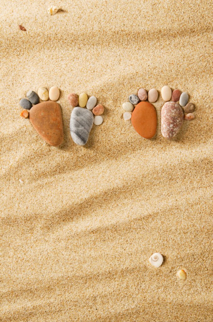 Two pairs of feet made out of stones in the sand, Kay Blowes Podiatry, Podiatry clinic, podiatrist, foot specialist, foot clinic, Westbury, Warminster, Trowbridge